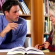 Stock Video: Lecturer helping his confused student in library