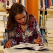 Stock Video: Student studying and taking notes in library surrounded by books