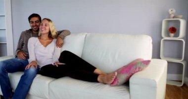かわいいカップル一緒にソファでリラックス — ストックビデオ