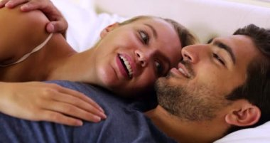 Cute couple chatting and cuddling in bed — Stock Video