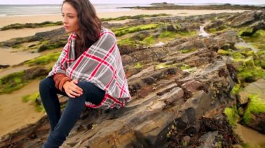 Brunette wrapped in a blanket sitting by the beach — Vídeo Stock