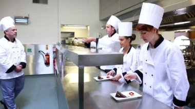 Head chef inspecting his students desserts — Stock Video