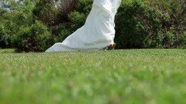 Bride in wedding dress walking on grass — Stock Video