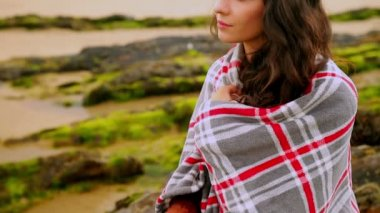 Brunette wrapped in a blanket sitting by the beach — Stock video