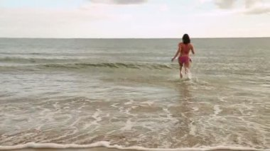 Energetic fit brunette running into the ocean — Stock Video