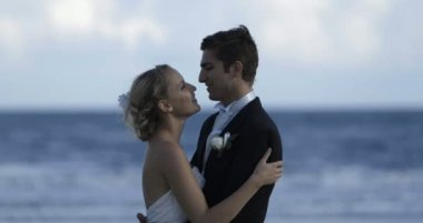 Cute newlywed couple embracing at the beach — Vídeo Stock