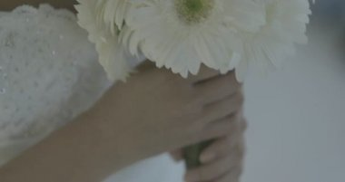 Beautiful bride holding bouquet of daisies — Stock Video