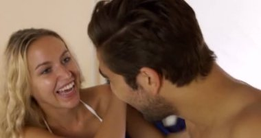 Laughing young couple having a pillow fight — Stock Video