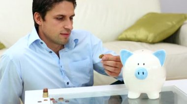 Man putting money into a piggy bank — Stock Video