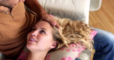 Blonde lying on the lap of her laughing boyfriend on the couch — Stockvideo