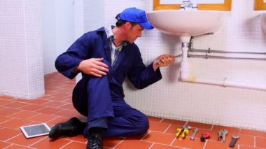 Handsome plumber fixing sink and checking tablet pc — Stock Video