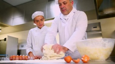 Head chef showing trainee how to prepare dough — Stock Video
