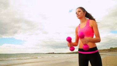 Beautiful brunette lifting dumbbells on the beach — Stock Video