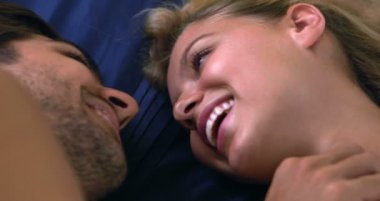 Happy couple lying in bed talking and laughing — Stock Video