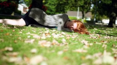 Peaceful napping redhead lying on green lawn — Stock Video
