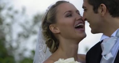 Laughing newlyweds kissing outside — Stock Video