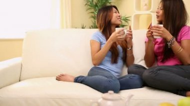 Sisters sitting on couch holding mugs — 图库视频影像