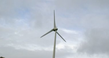 Windmill spinning against a grey sky — Wideo stockowe