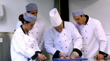 Head chef showing his trainees how to fillet a salmon — Stock Video