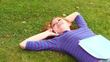 Smiling student lying on grass talking on the phone — Stock Video