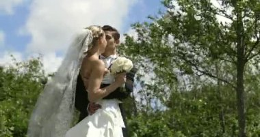 Groom kissing his pretty new wife outside — Stock Video
