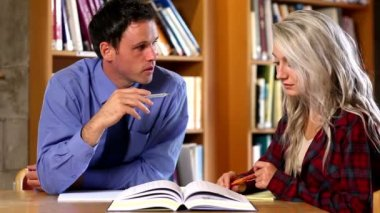 Lecturer helping his confused student in the library — Wideo stockowe