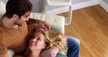 Girlfriend lying on the lap of her boyfriend on the couch — Wideo stockowe