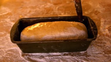 Olive oil being brushed over dough in loaf tin on a floury table — Stock Video