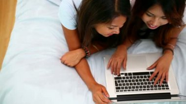 Beautiful happy sisters lying on bed using laptop — Stock Video