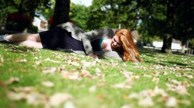 Cheerful redhead relaxing lying on green lawn — Stock Video