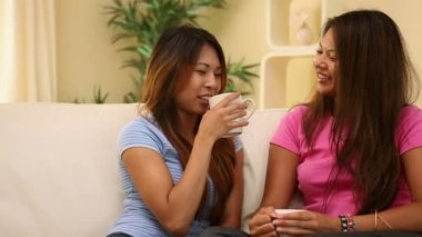 Sisters sitting on couch holding mugs — Vídeo Stock