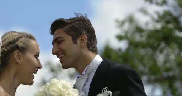 Les nouveaux mariés s'embrassant à l'extérieur sur un jour de grand vent en riant — Vidéo