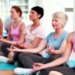 Stock Video: Women in fitness studio doing yoga
