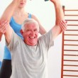 Elderly man lifting hand weights sitting on exercise ball with his trainer — Video Stock #39158967