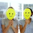 ストックビデオ: Business team holding smiley face balloons