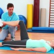 Trainer helping his client bend her knee — Stock Video #39159345