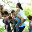 Stock Video: Fit group of friends having fun and messing in the park