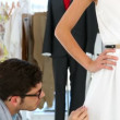 Stock Video: Designer adjusting hemline of dress on model