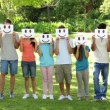 Group of casual young friends holding smiley faces over their faces — стоковое видео #39159553