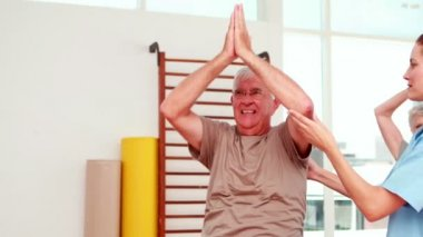 Injured senior citizen exercising with physiotherapist — Stock Video