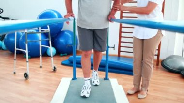 Physiotherapist helping patient walk with parallel bars — Stock Video