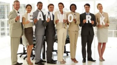 Happy business people holding letters spelling teamwork — Stock Video