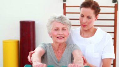 Physical therapist helping patient lift hand weights — Stock Video