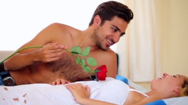 Man tickling his girlfriend with a rose on bed — Stock Video