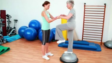 Trainer helping elderly client to use bosu ball — Stock Video