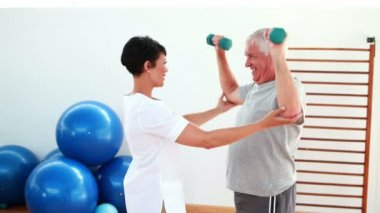 Pretty physiotherapist helping elderly patient lift hand weights — Stock Video
