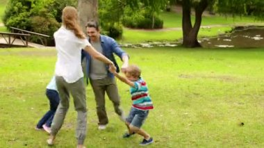 Happy family playing ring a rosie in the park together — Stock Video