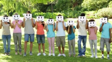 Group of casual young friends holding smiley faces over their faces — Stockvideo