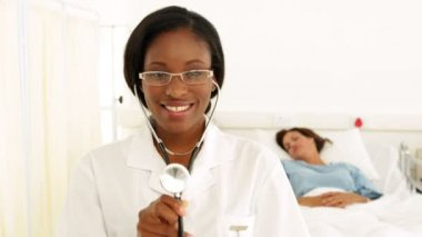 Smiling nurse in the ward holding her stethoscope — Stok video