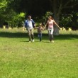 Little boy and parents running towards camera in the park holding hands — Stock Video